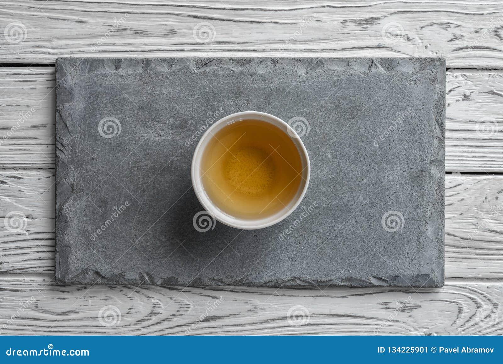 Grå konkret platta på ljus träbakgrund och en kopp te