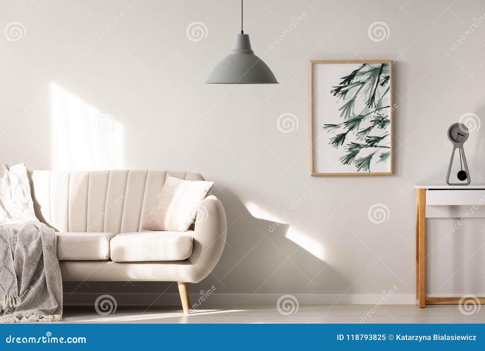 Grå lampa i ljus vardagsruminre med affischen bredvid bei
