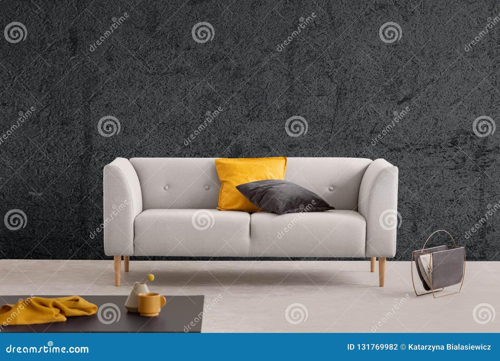 Grå soffa i vardagsrum som är inre med den texturerade väggen och tabellen Verkligt foto