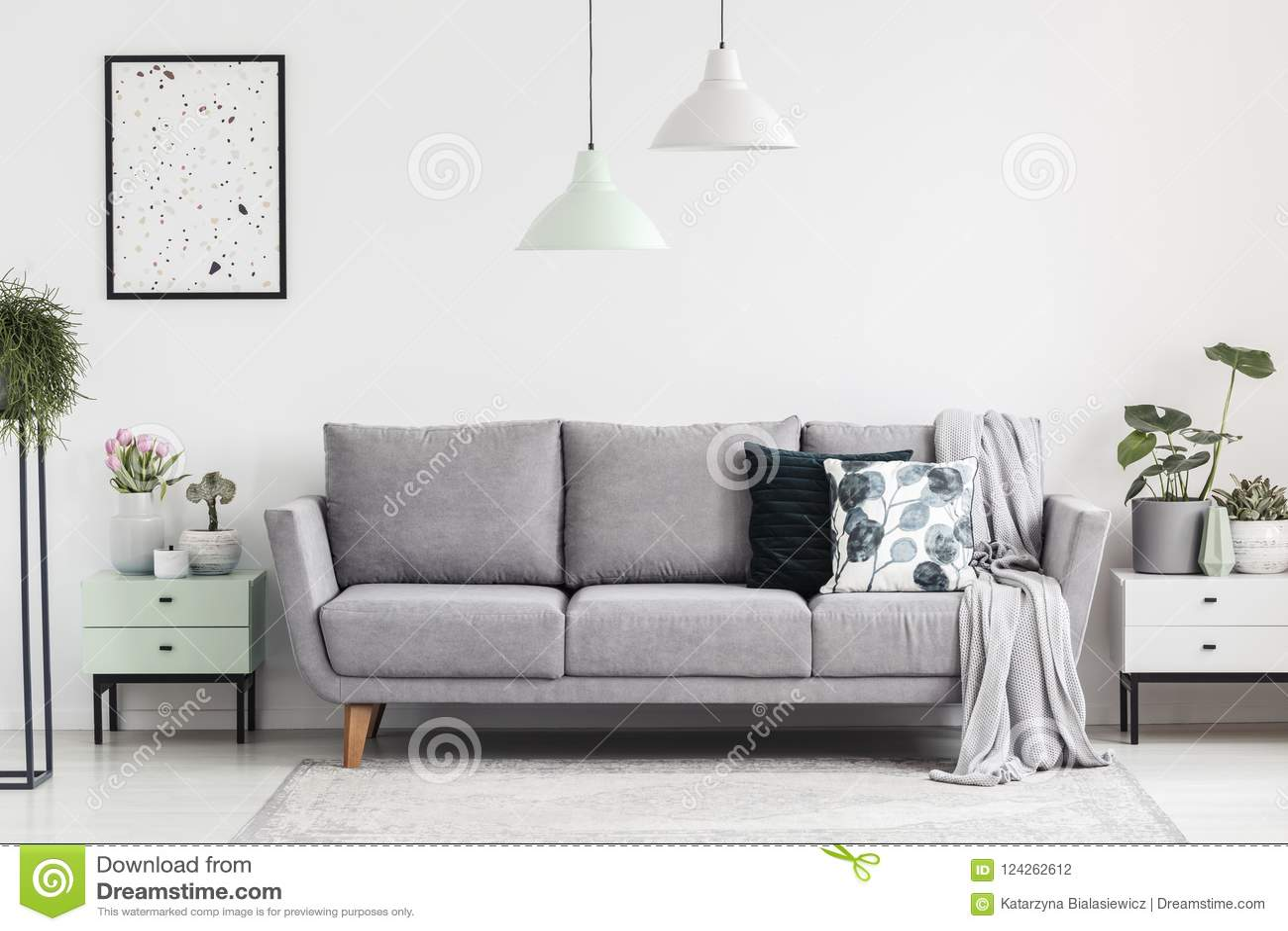 Grå soffa mellan kabinetter med växter i vit vardagsruminte