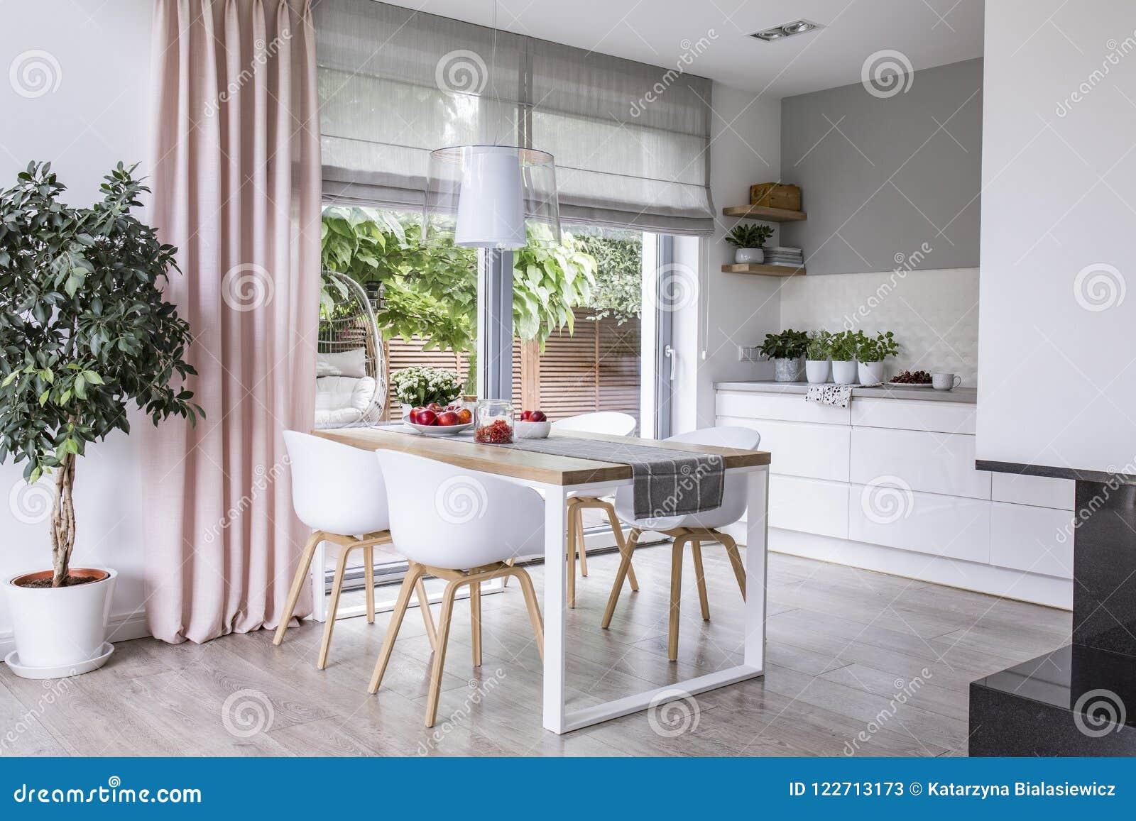 Gråa roman skuggor och en rosa gardin på stora glass fönster i a