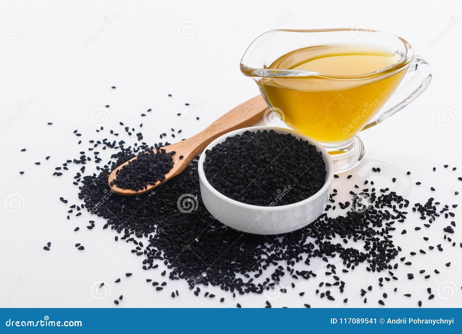 Grões do cominhos e do óleo pretos no fundo rústico