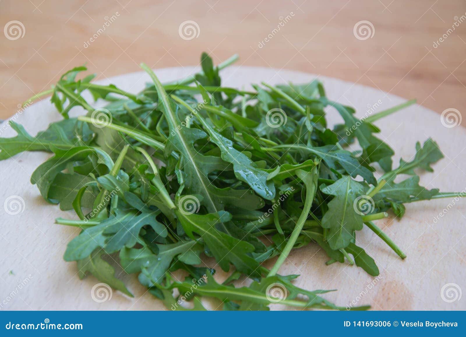 Grön arugula lämnar på träskärbräda Ny rucola i köket i det plast- magasinet, italiensk smaktillsats Sund livsstil