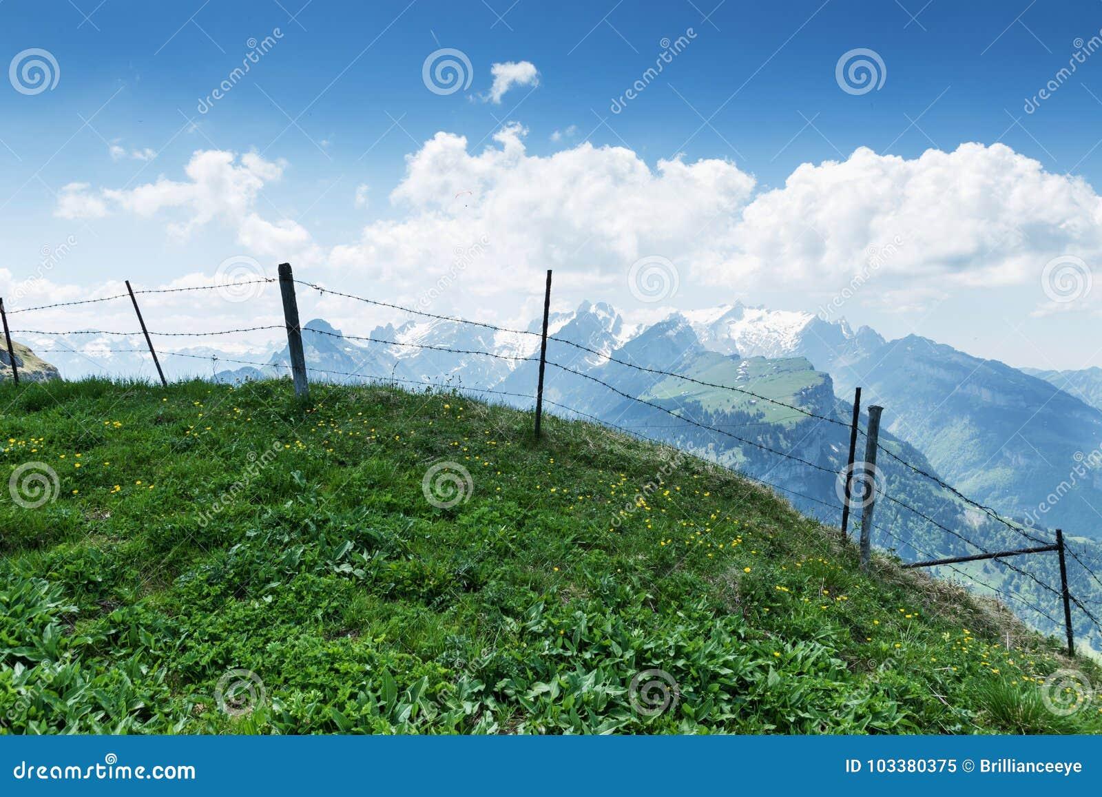 Grön bergäng framme av försett med en hulling - trådstaket och sikt till