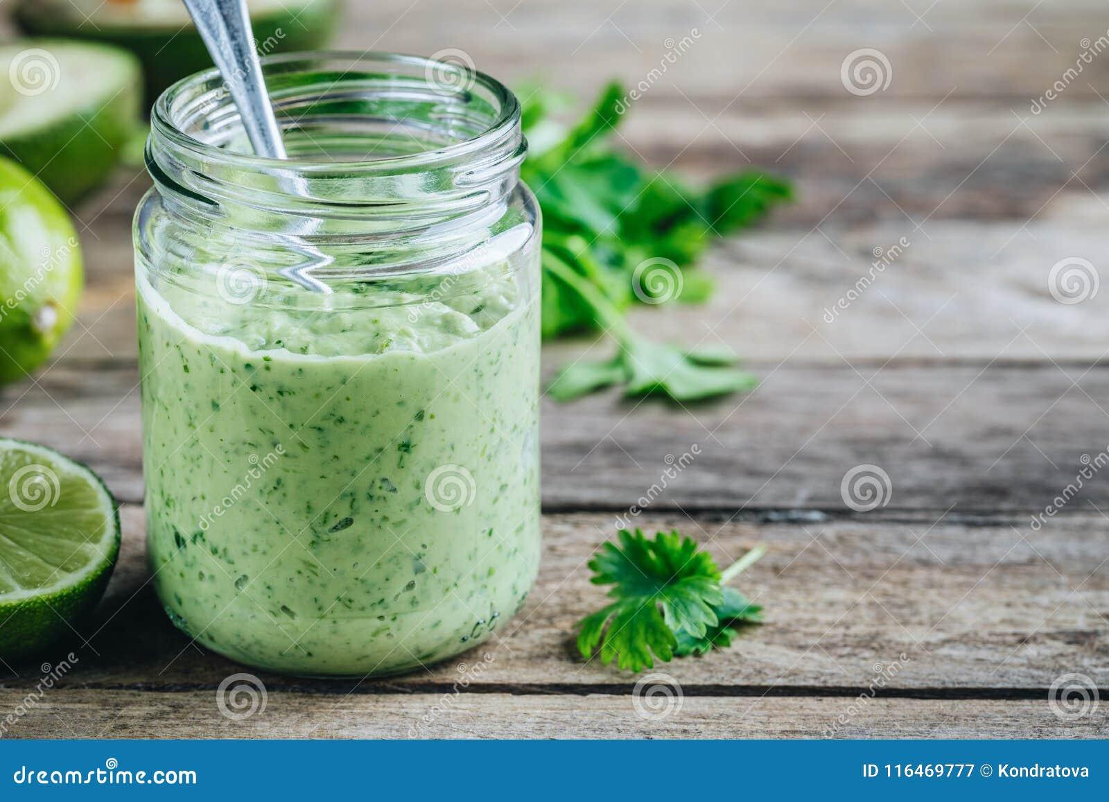 Grön dressing med avokadot, limefrukt och koriander i en glass krus