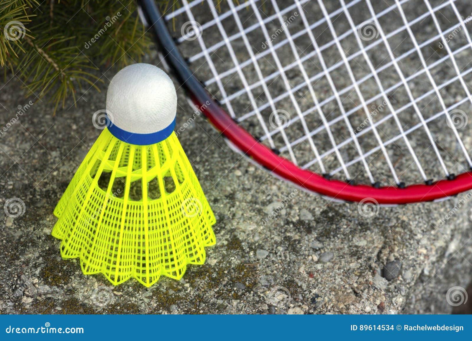 Grön fjäderboll för neon och röd benägenhet för badmintonracket på stenen
