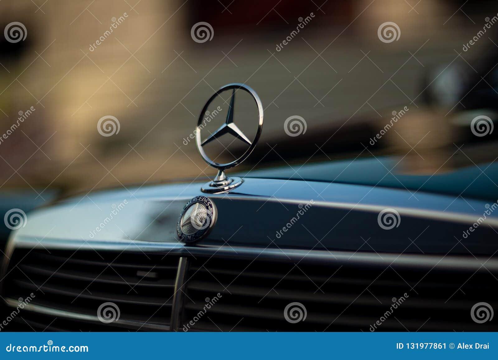 Grön Mercedes-Benz för gammal sällsynt tappning huv, emblem, elementskyddsgaller på suddig bakgrund Symbolet av rikt liv