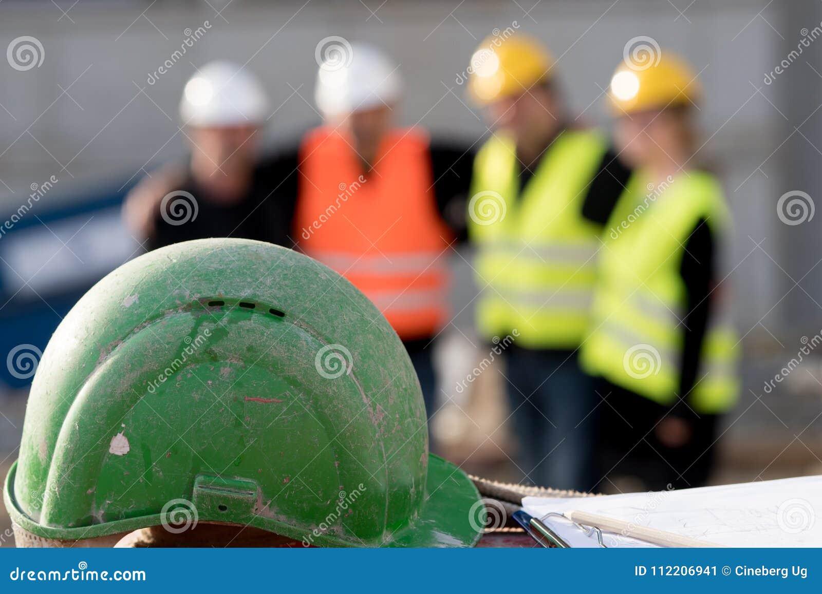 Grön säkerhetshjälm på förgrund Grupp av fyra byggnadsarbetare som poserar på ut ur fokuserad bakgrund