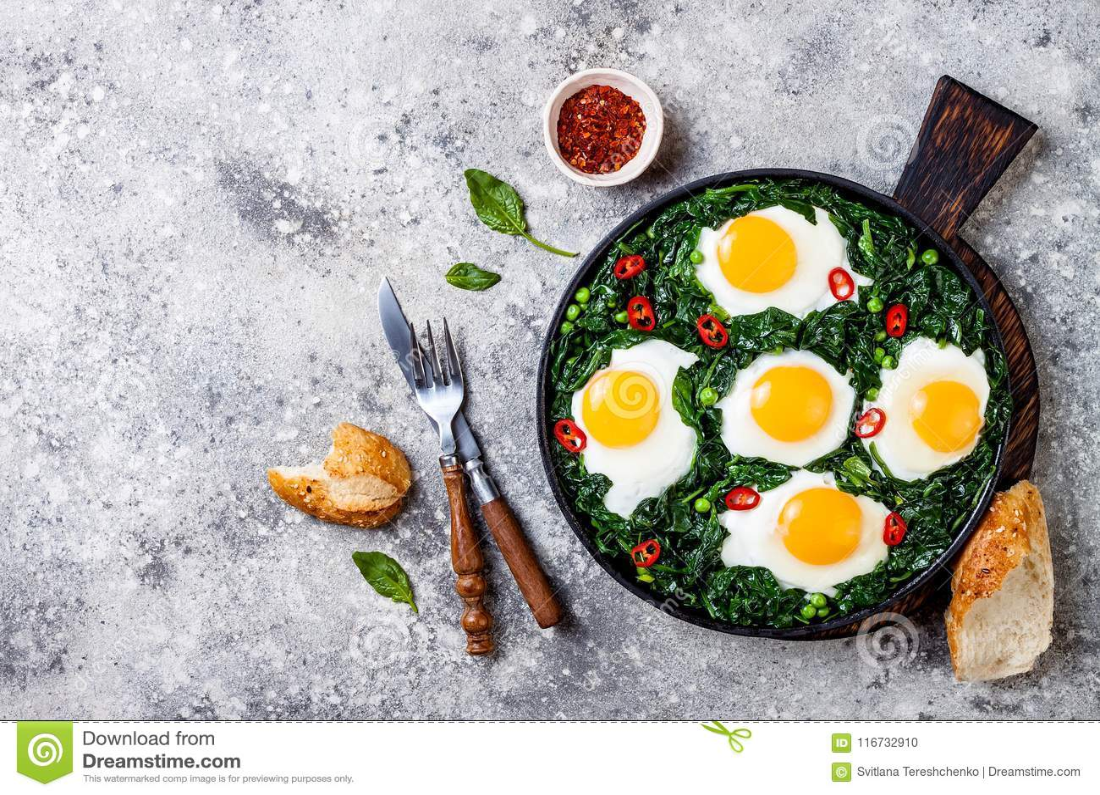 Grön shakshuka med spenat, grönkål och ärtor Lägger den bästa sikten för den sunda läckra frukosten, över huvudet som är plan
