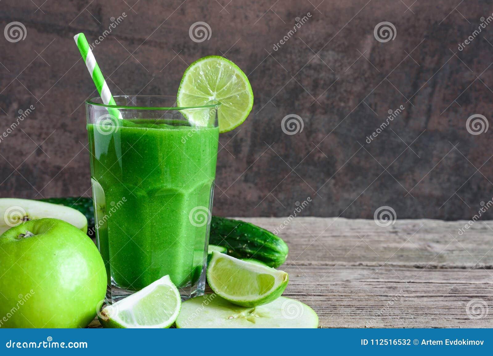 Grön sund smoothie i ett exponeringsglas med spenat, äpplet, gurkan och limefrukt med ett sugrör Detoxdrink
