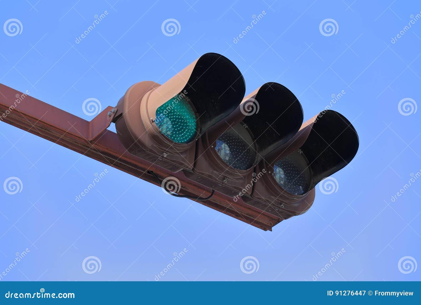 Grön trafikljus under bakgrund för blå himmel
