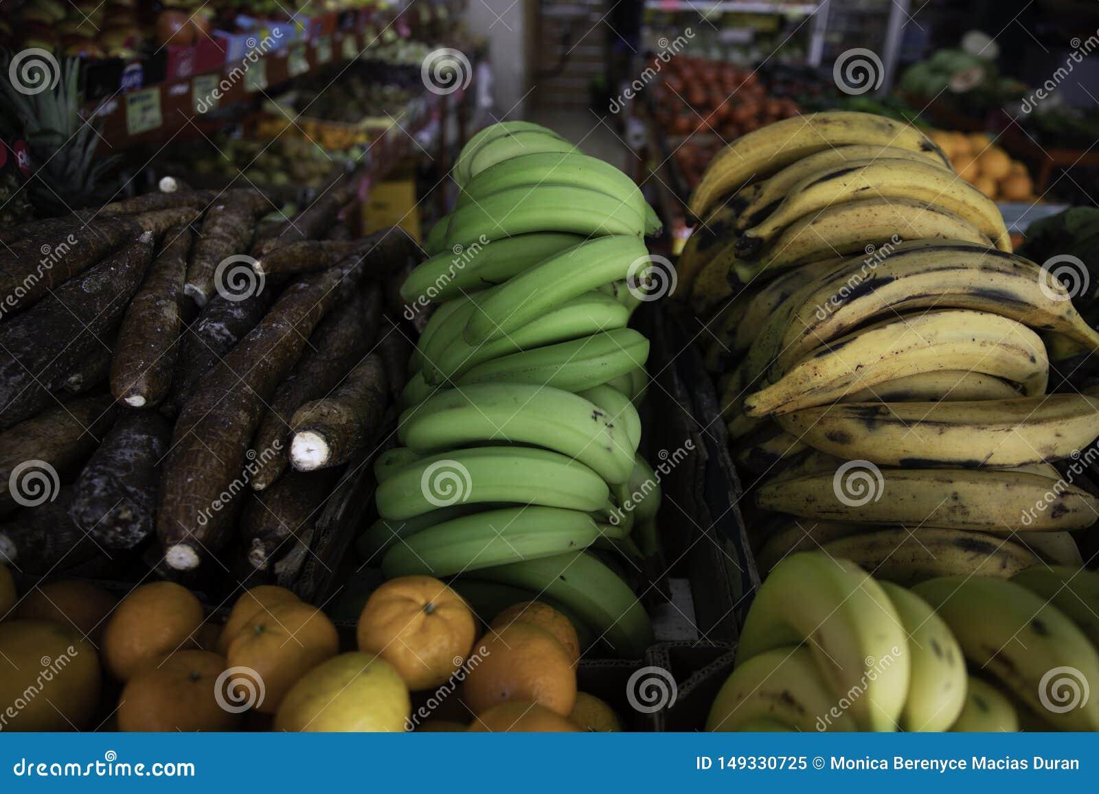 Gr?na och gula bananer i fruktaff?r
