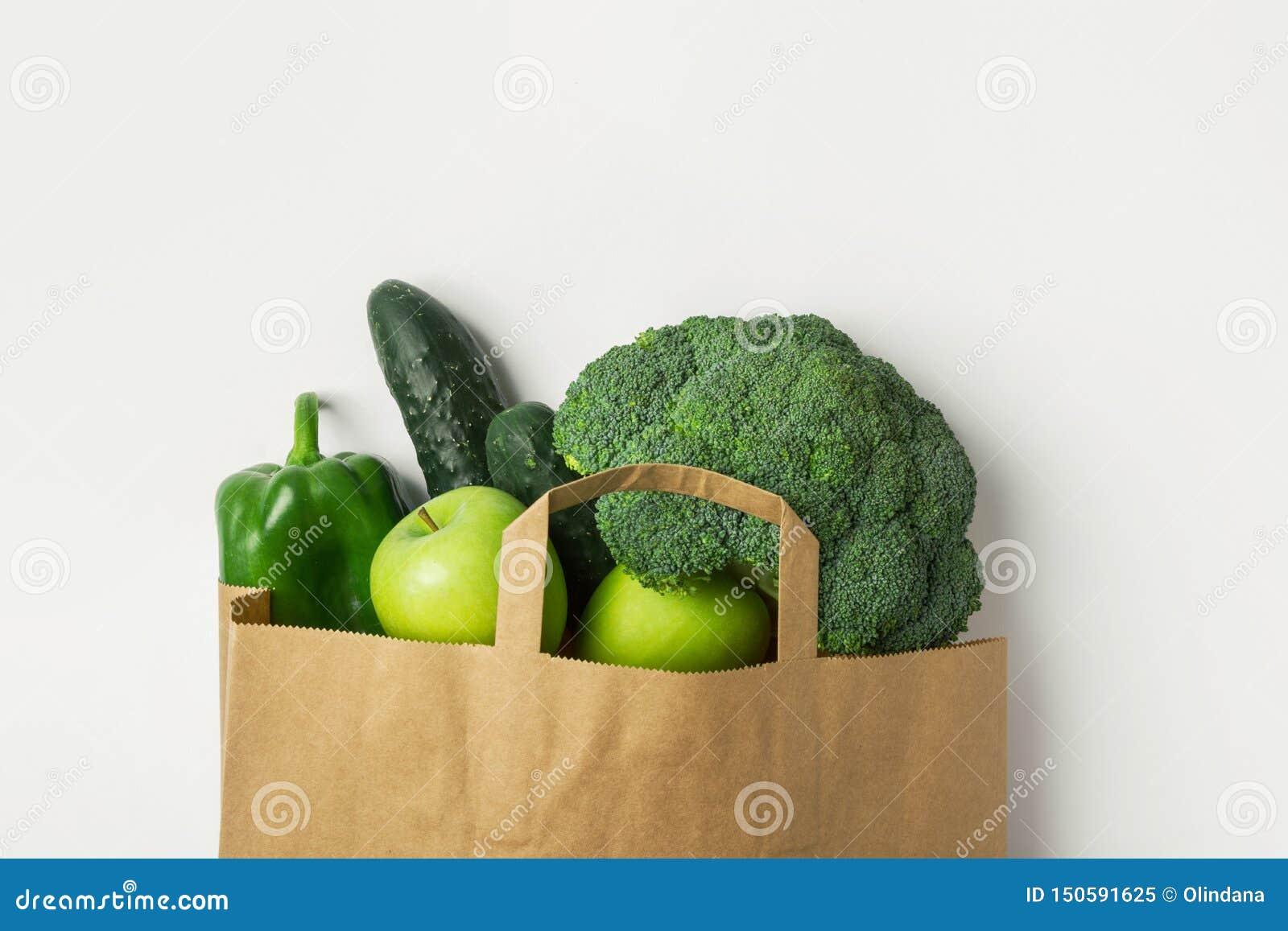 Gröna rå organiska äpplen för spanska peppar för gurkor för grönsakfruktbroccoli i brun påse för livsmedelsbutik för Kraft papper