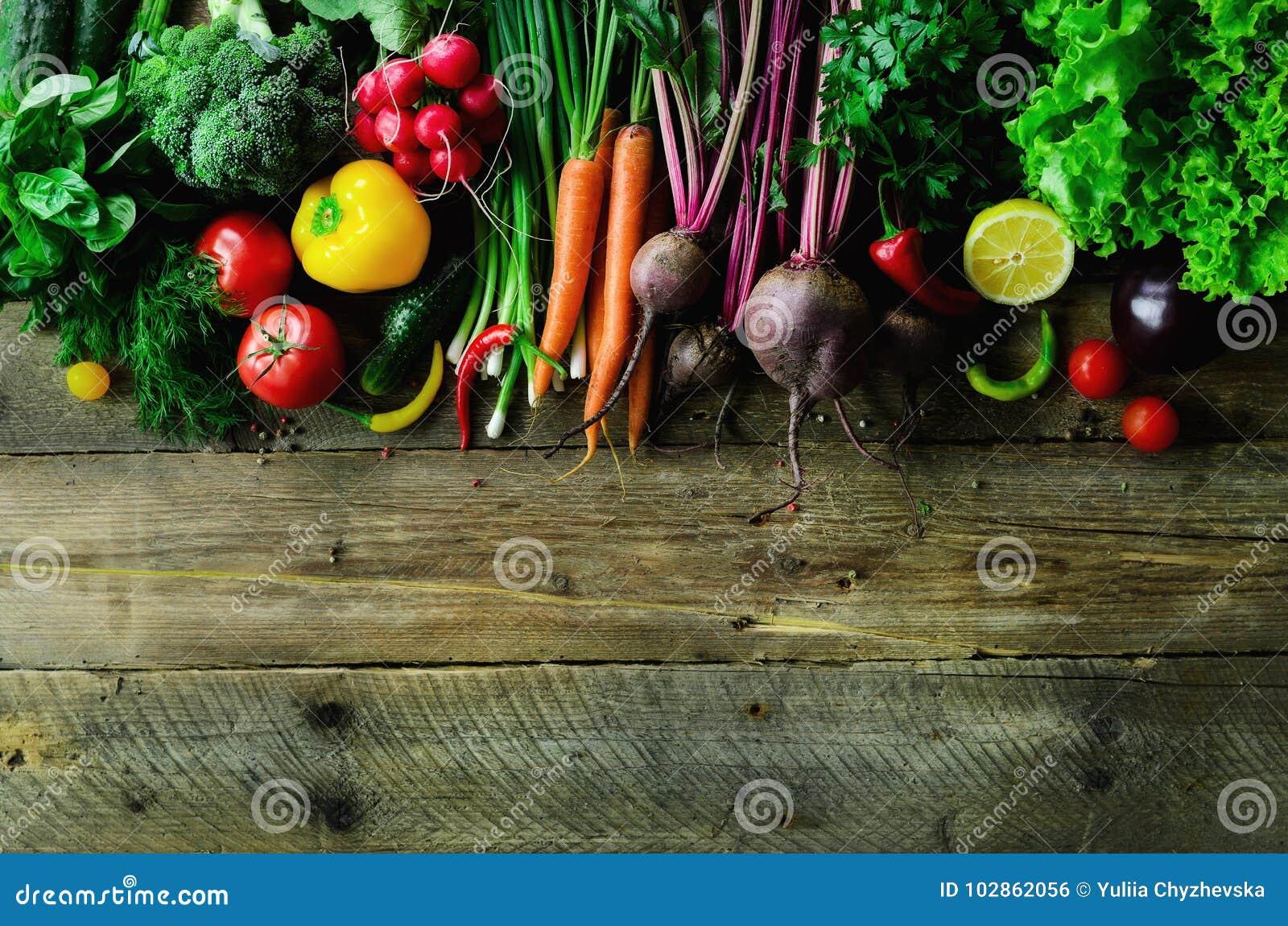 Grönsaker på träbakgrund Bio sunda organisk mat, örter och kryddor Rått och vegetariskt begrepp ingredienser