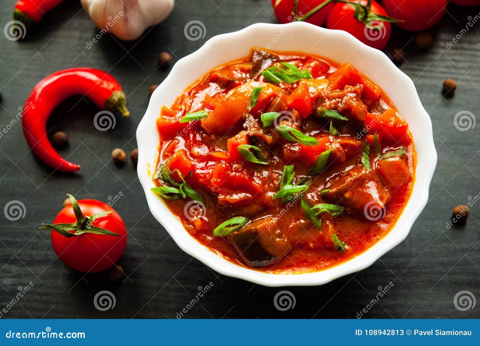 Grönsakrague med aubergine, peppar, tomaten och moroten i den vita bunken på mörk träbakgrund
