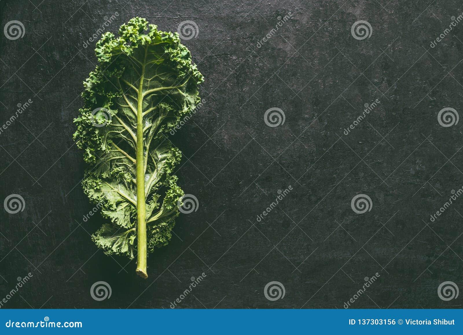 Grönt grönkålblad på mörk bakgrund, bästa sikt med kopieringsutrymme Sunda detoxgrönsaker Rent äta och banta begrepp överkant