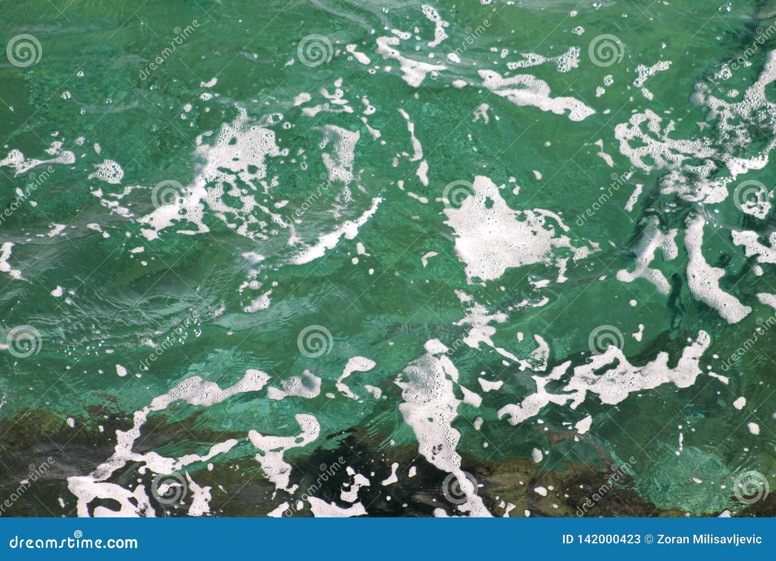 Grönt havsvatten för turkos med havsskum som bakgrund, slut upp Yttersida av havet med vågor, färgstänk, skum och bubblor