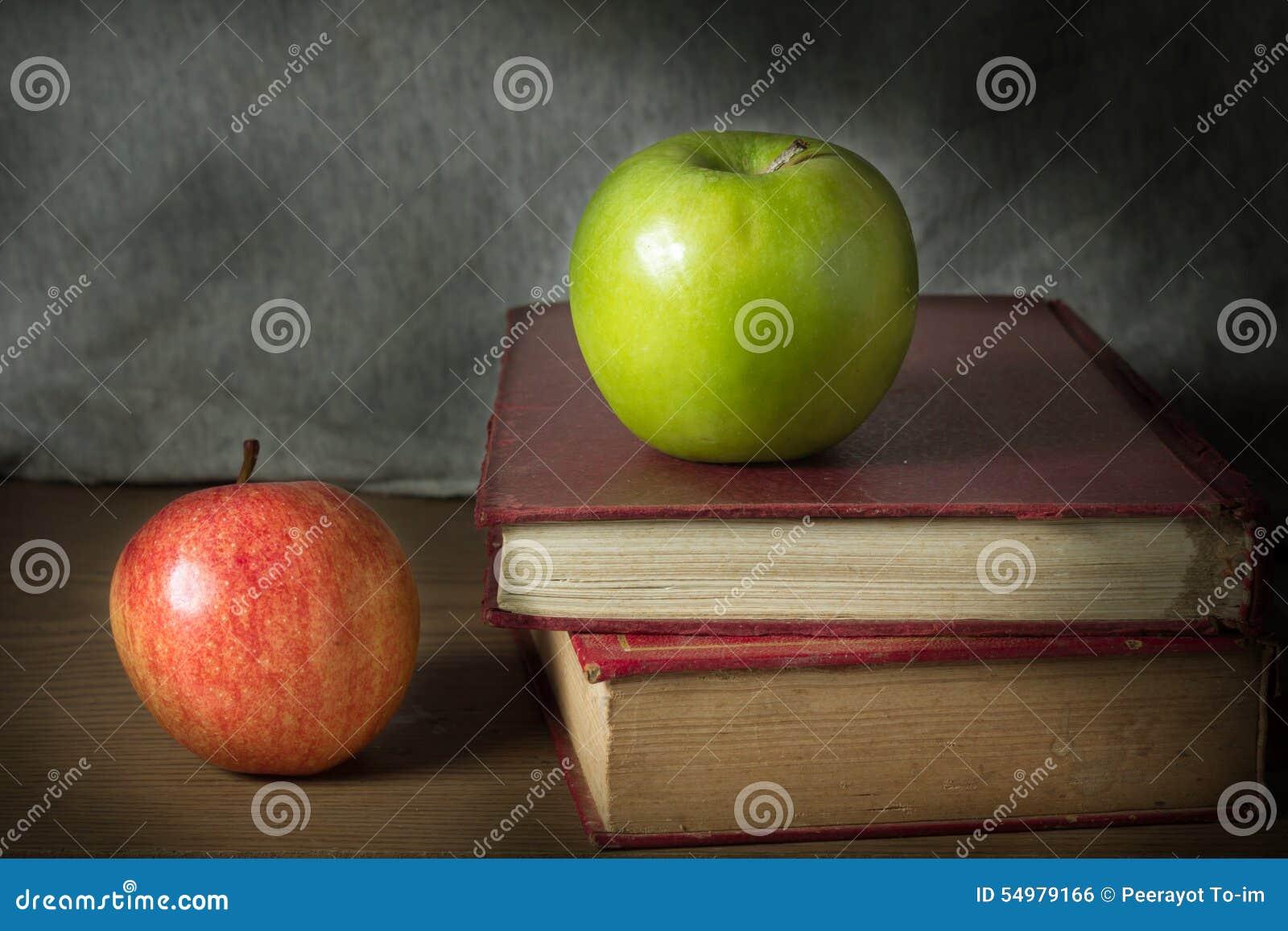 Grönt och rött äpple med antika böcker