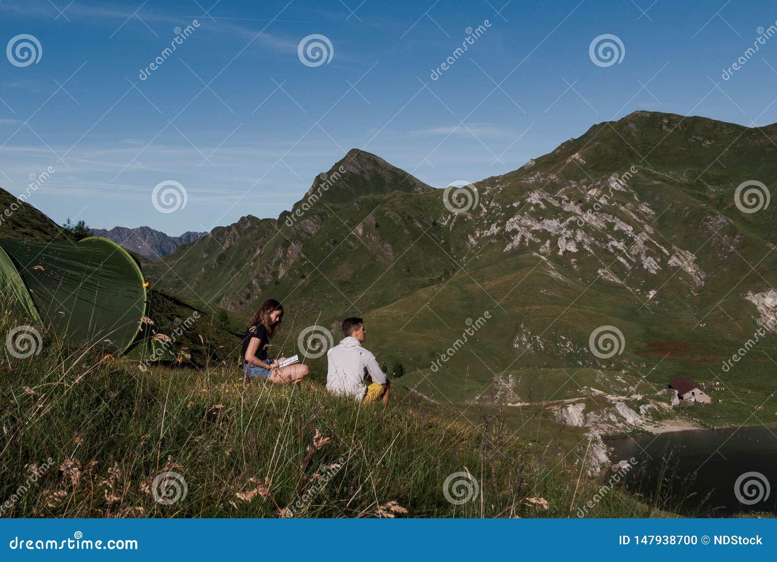 Grönt tält som förläggas i ett fridsamt ner i bergen av Schweiz Flickan som läser en bok, pojke beundrar sikten