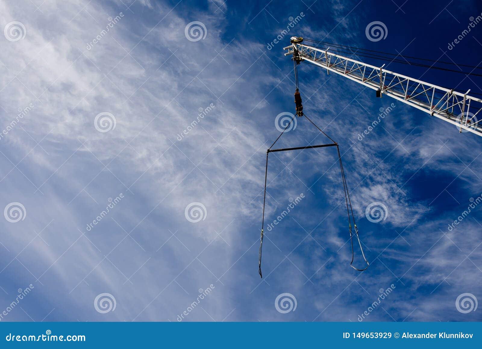 Grúa del auge con un cable contra el cielo azul Fondo Copie el espacio