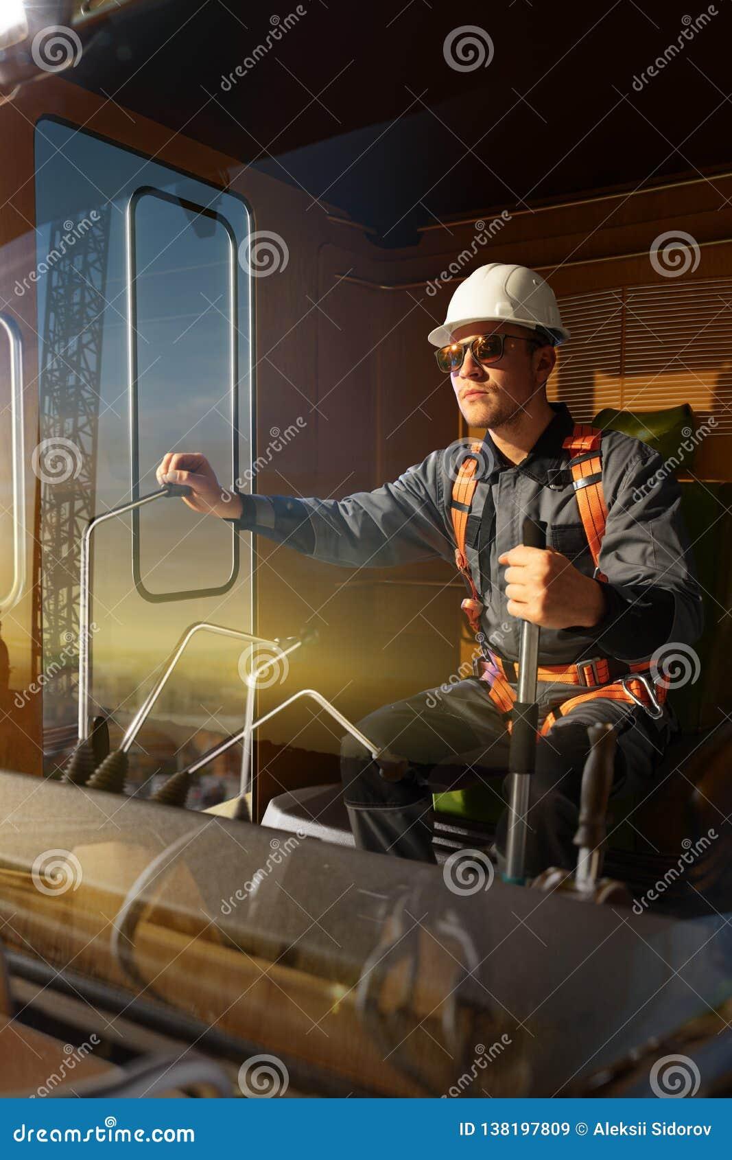 Grúa del operador del ingeniero en la acción Él sienta un top en cabina y el trabajo de la grúa