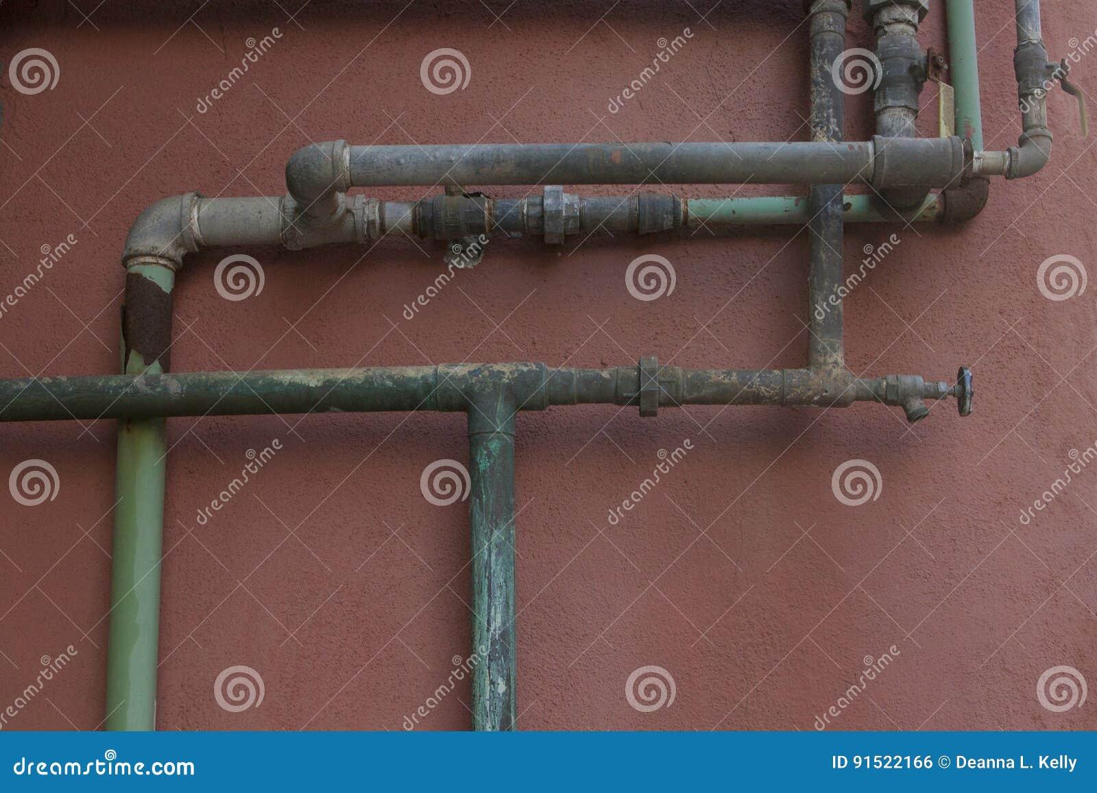 Grün und Aqua Rusty Pipes auf Coral Stucco Wall