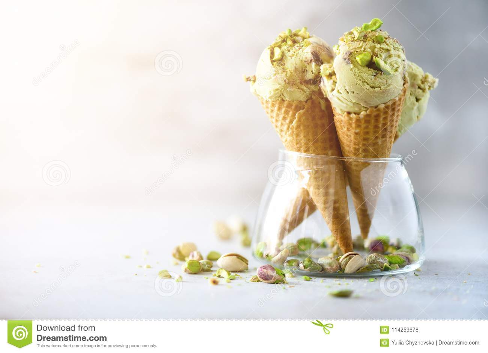 Grüne Eiscreme im Waffelkegel mit Schokolade und Pistazien auf grauem Steinhintergrund Sommerlebensmittelkonzept, Kopie