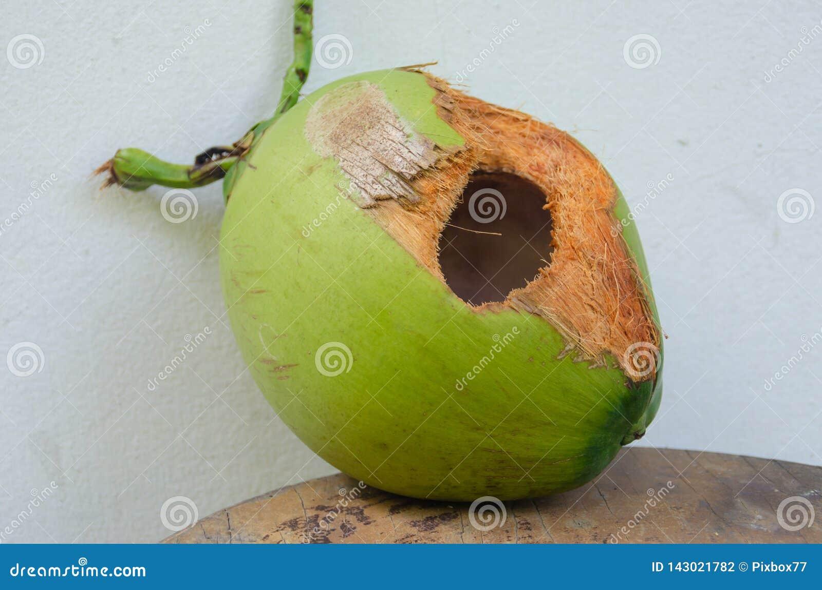 Grüne Kokosnuss mit Loch auf Tabelle