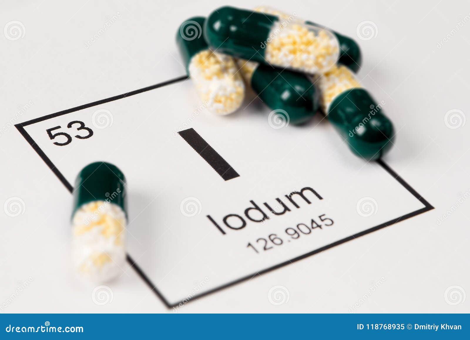 Grüne Pillen mit Mineral I Iodium auf einem weißen Hintergrund mit a