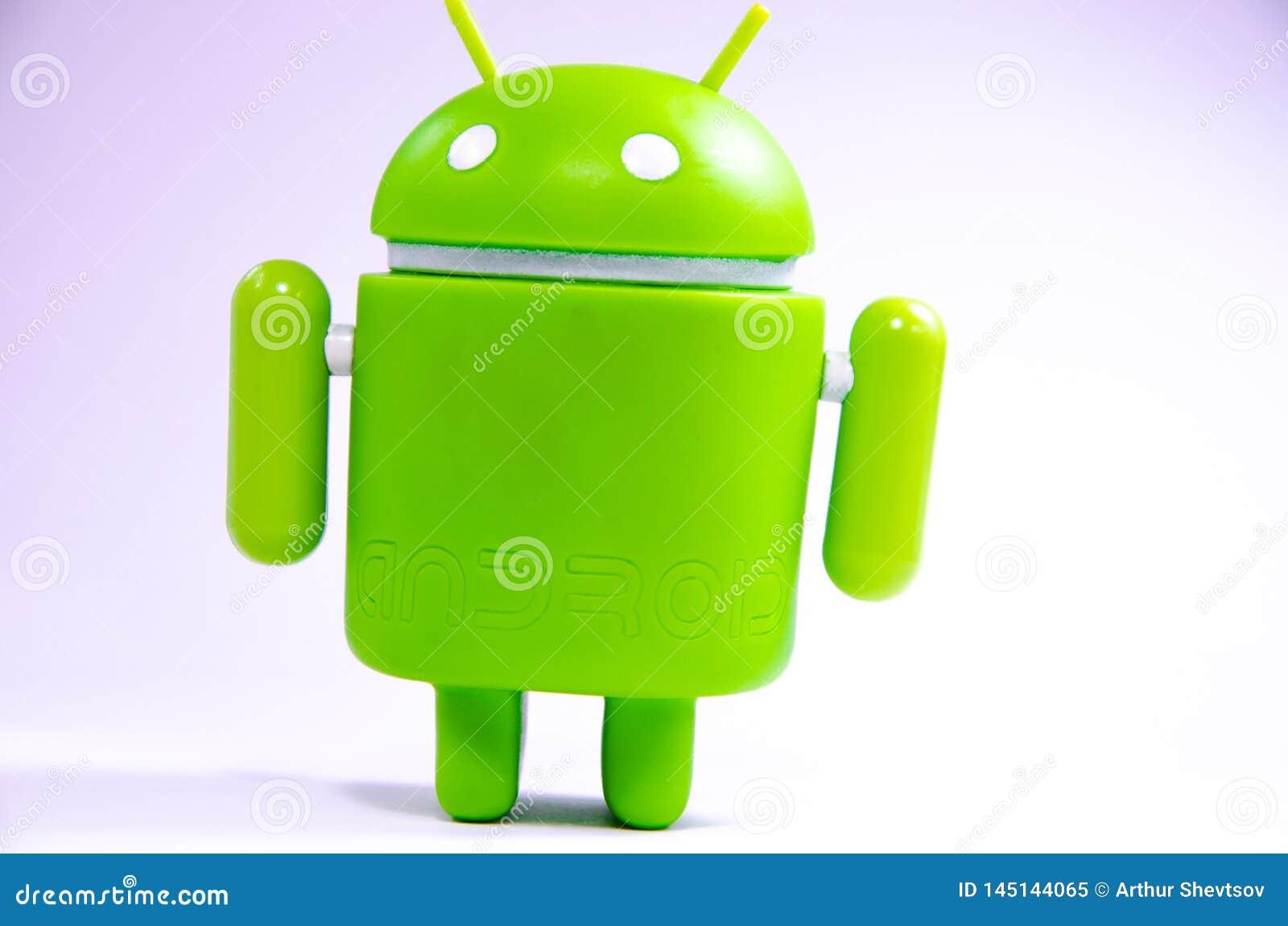Gr?ne Plastik-Android-Zahl auf einem wei?en Hintergrund und mit einem Smartphone