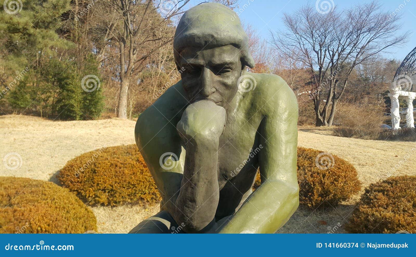 Grüne Statue des Denkers Auguste Rodin, stellend nackt auf einem Felsen ein