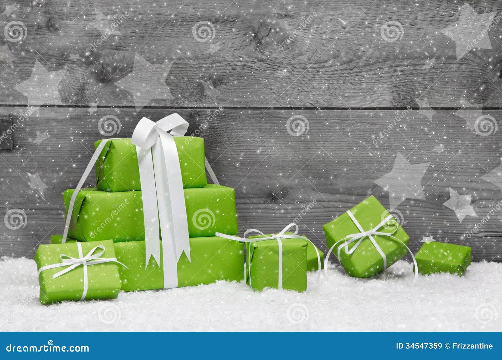 Grüne Weihnachtsgeschenke mit Schnee auf grauem hölzernem Hintergrund für