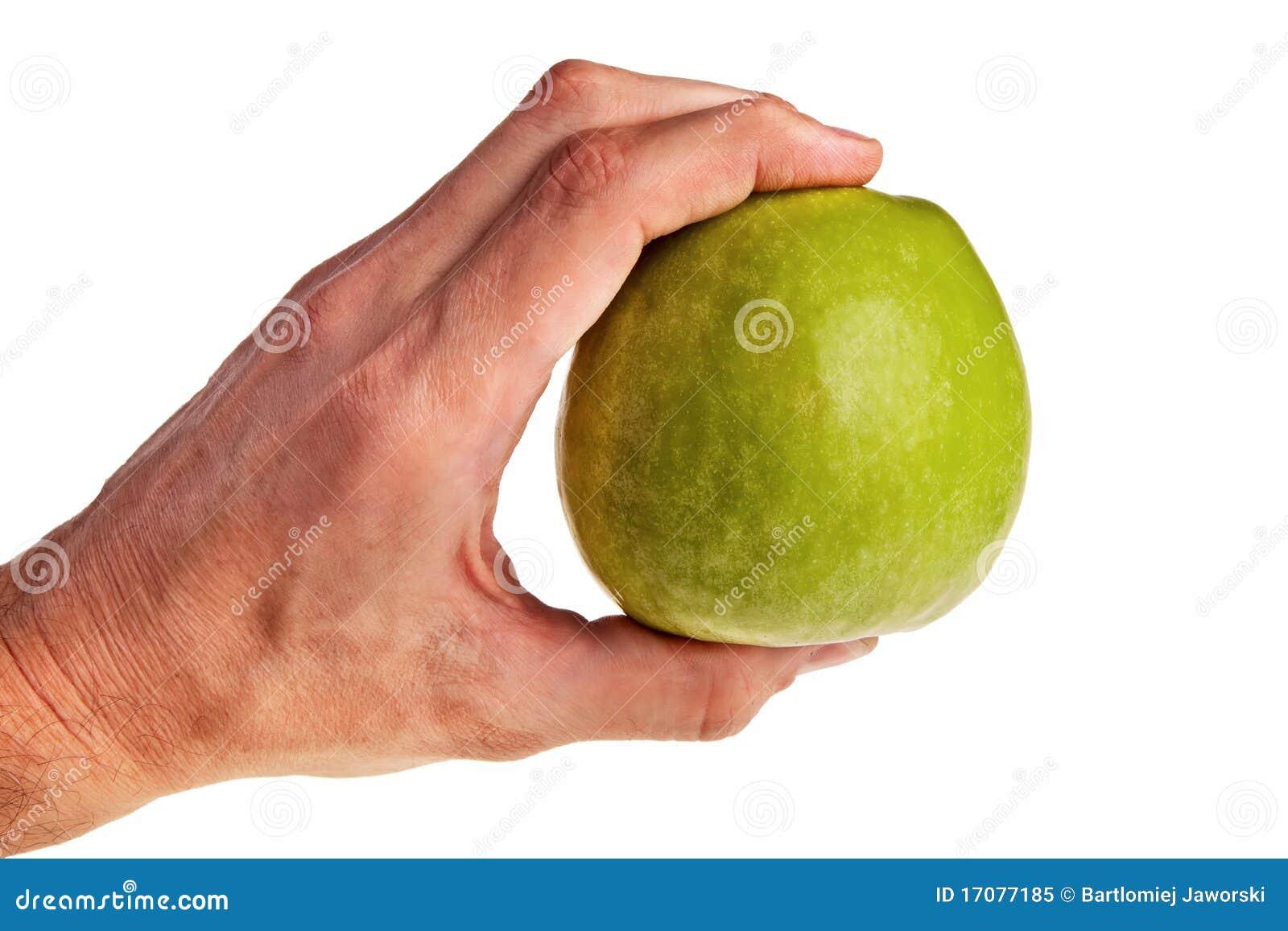 Grüner Apfeleinfluß durch weiße männliche Hand.