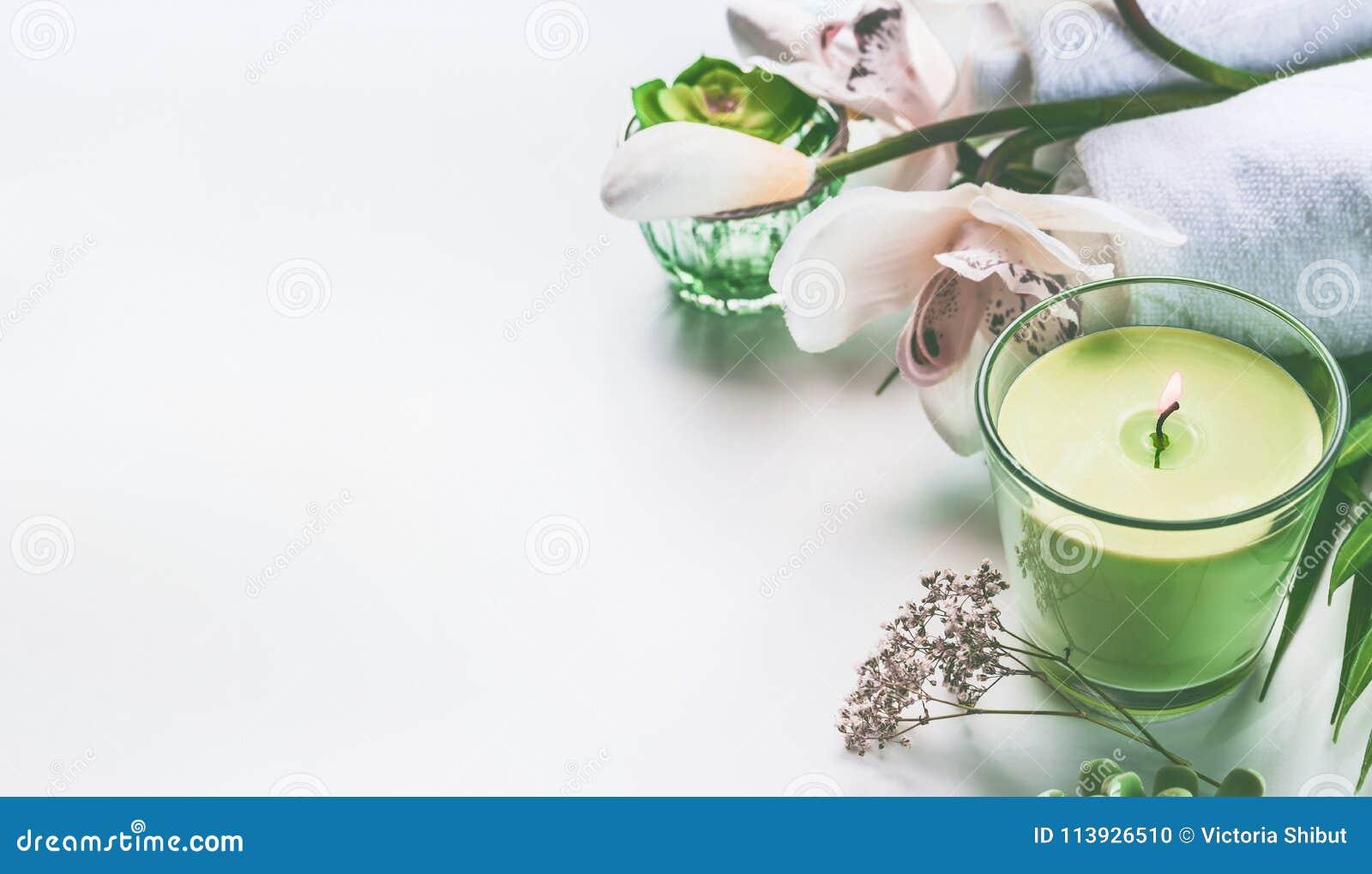 Grüner Badekurort- oder Wellnesshintergrund mit Tüchern, Kerze, Orchideenblumen und Zubehör