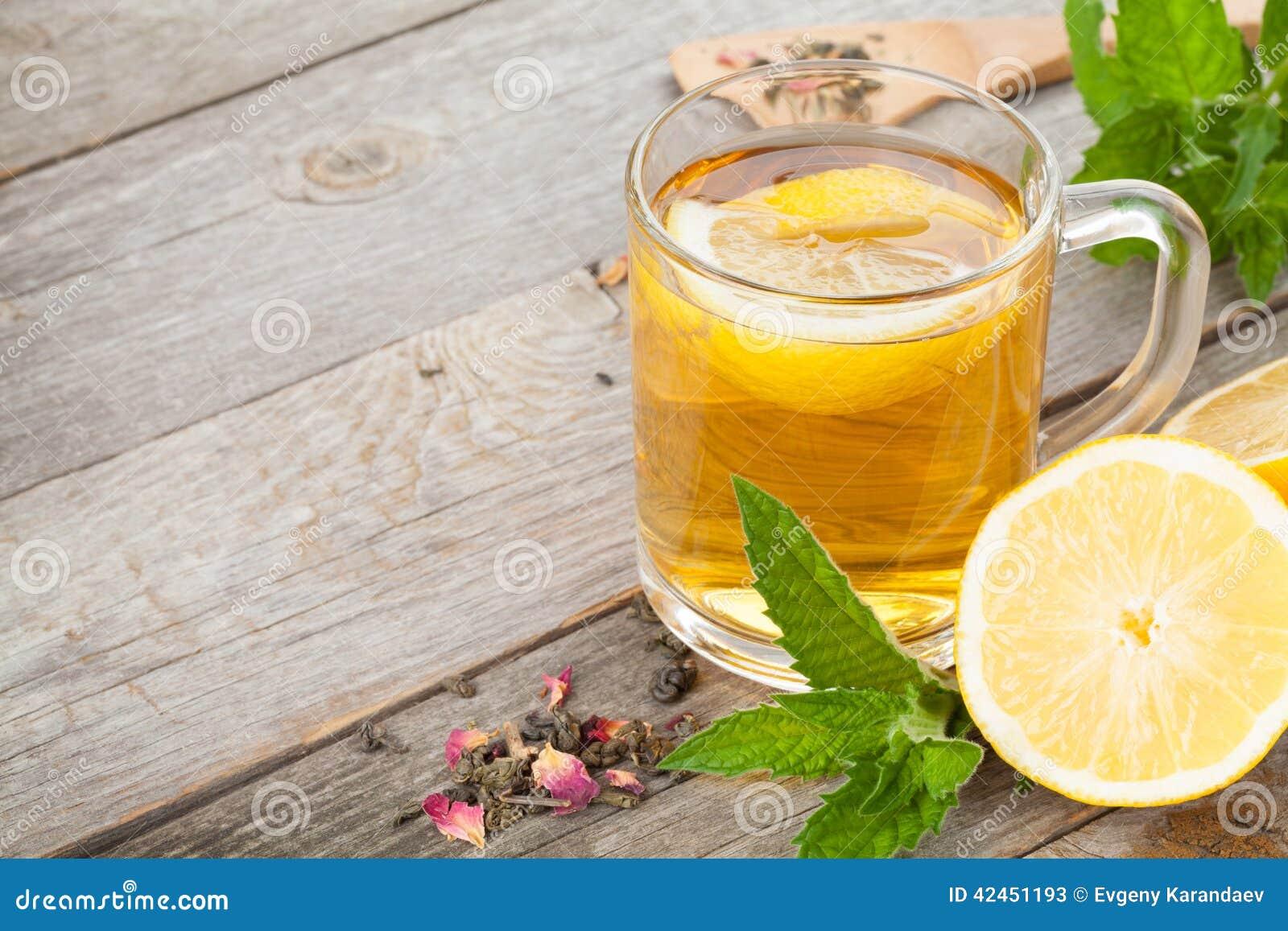 Grüner Tee mit Zitrone und Minze auf Holztisch