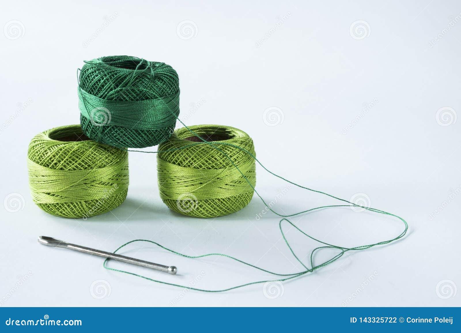 Grünes Häkelgarn mit Scheren und Nadel Weißer Hintergrund,
