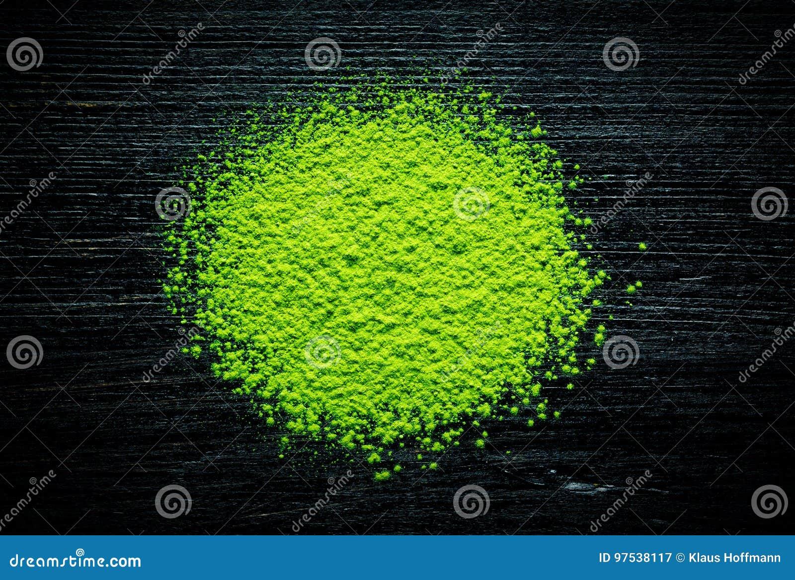 Grünes matcha Teepulver auf schwarzem Hintergrund