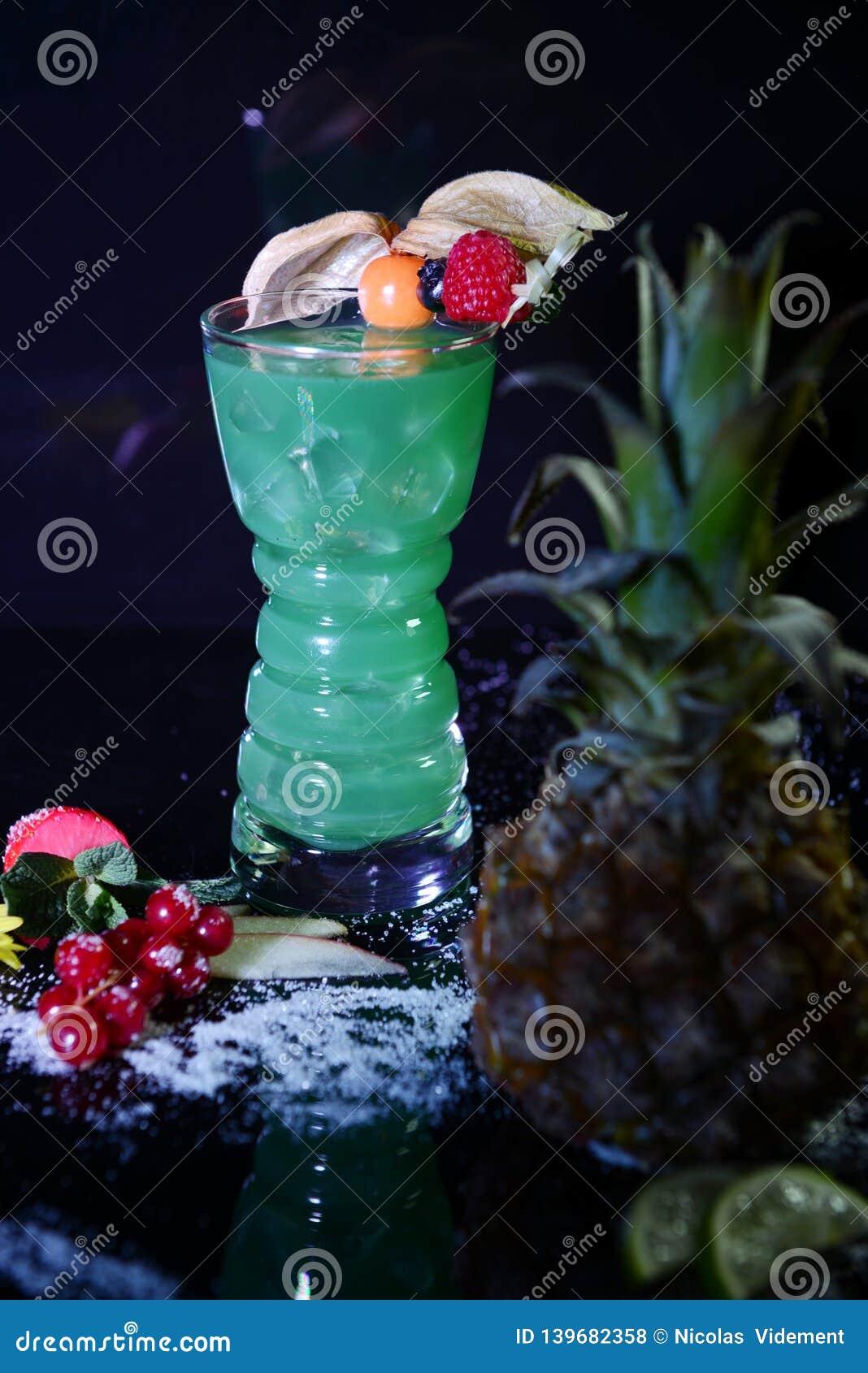 Grünes Neoncocktail mit Früchten auf schwarzem Hintergrund