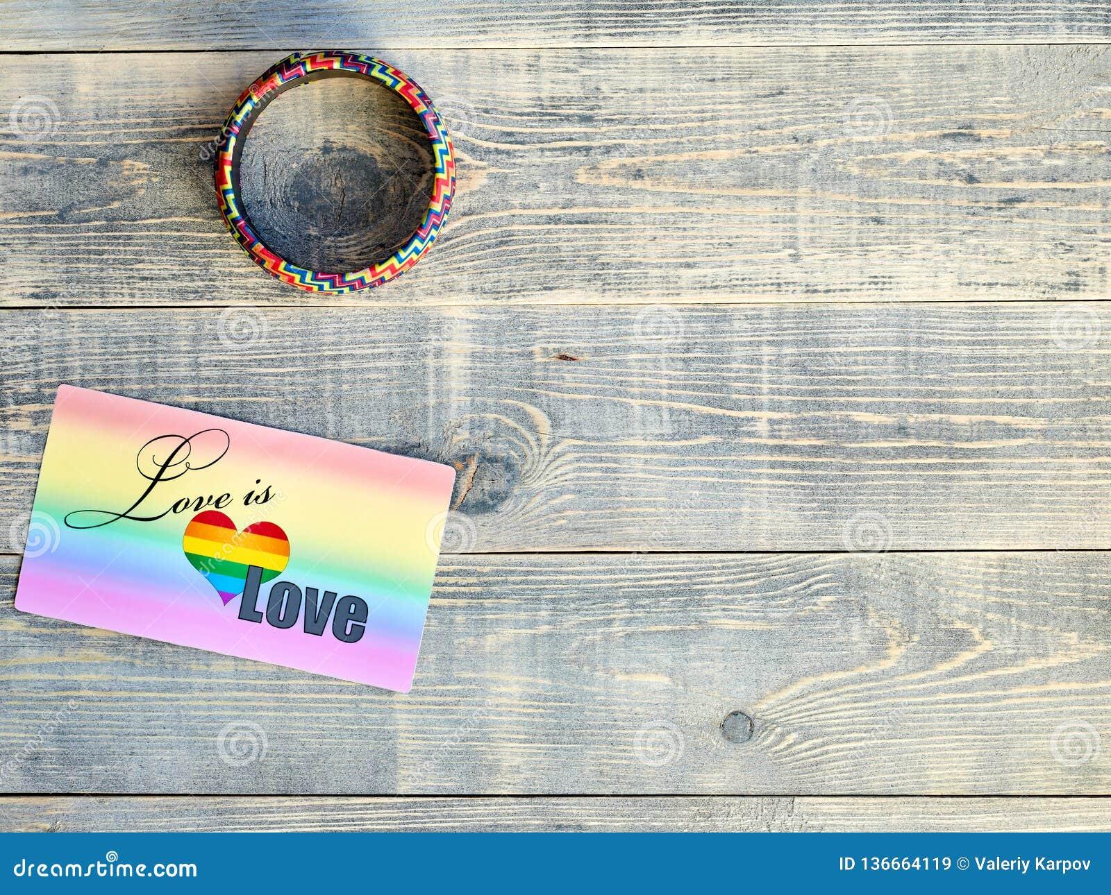 Grępluje który mówi miłość jest miłością z tęczy tłem i bransoletką na ręce z LGBTQ flagi LGBT kłamstwem na bławym