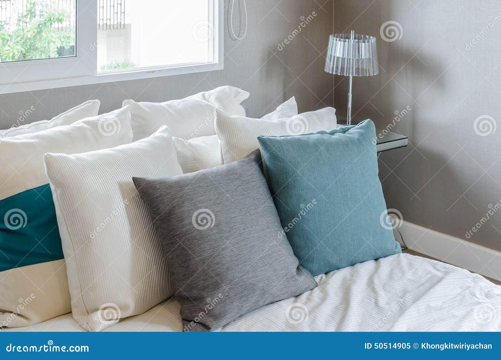 Grå färg  och gräsplankudde på vit säng i modernt sovrum arkivfoto ...