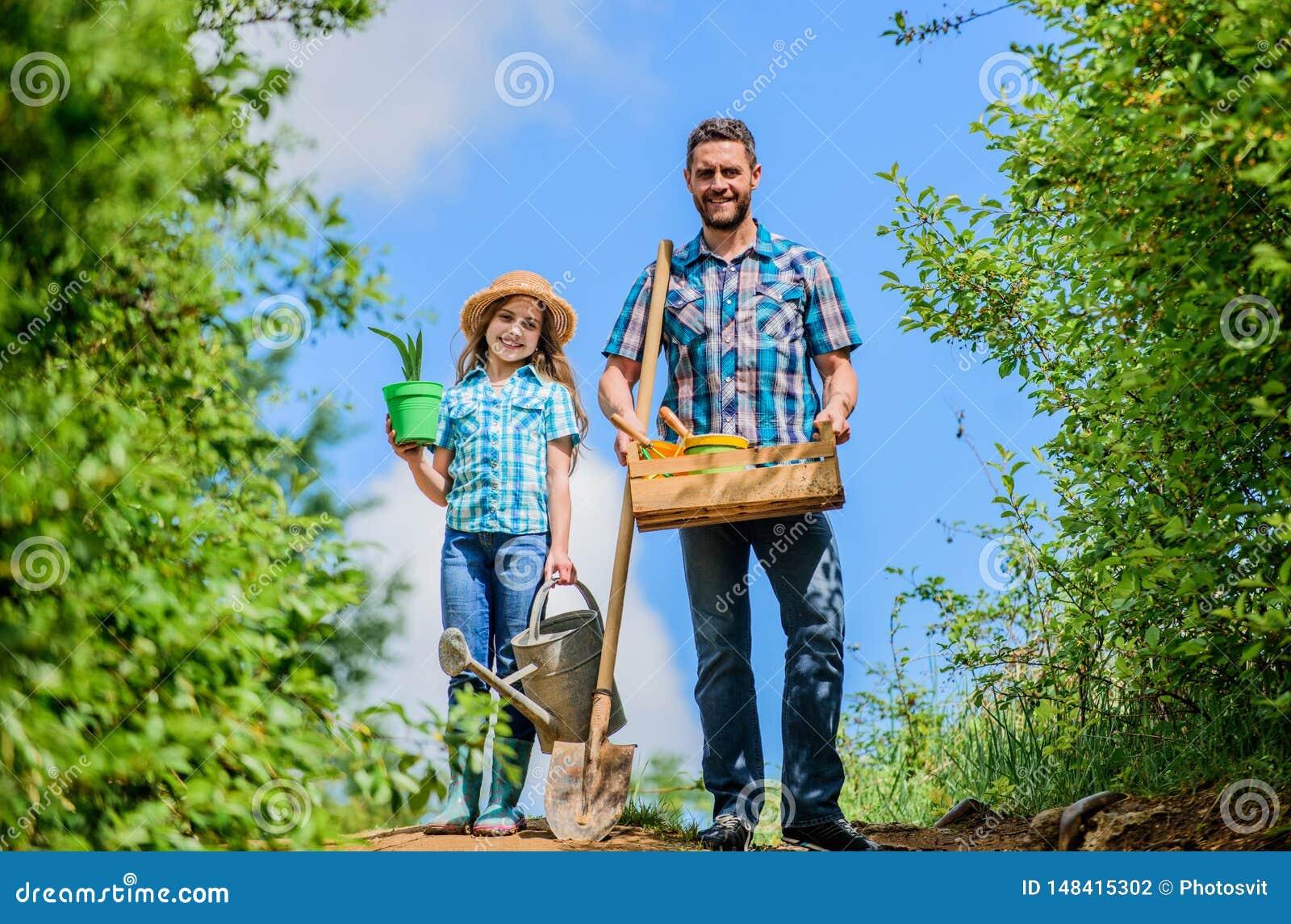 Gr?ne Lebensdauer Landwirtmann mit wenigem M?dchen Gartenwerkzeuge, -schaufel und -Gie?kanne Kinderarbeitskraft mit Vatigriffkast