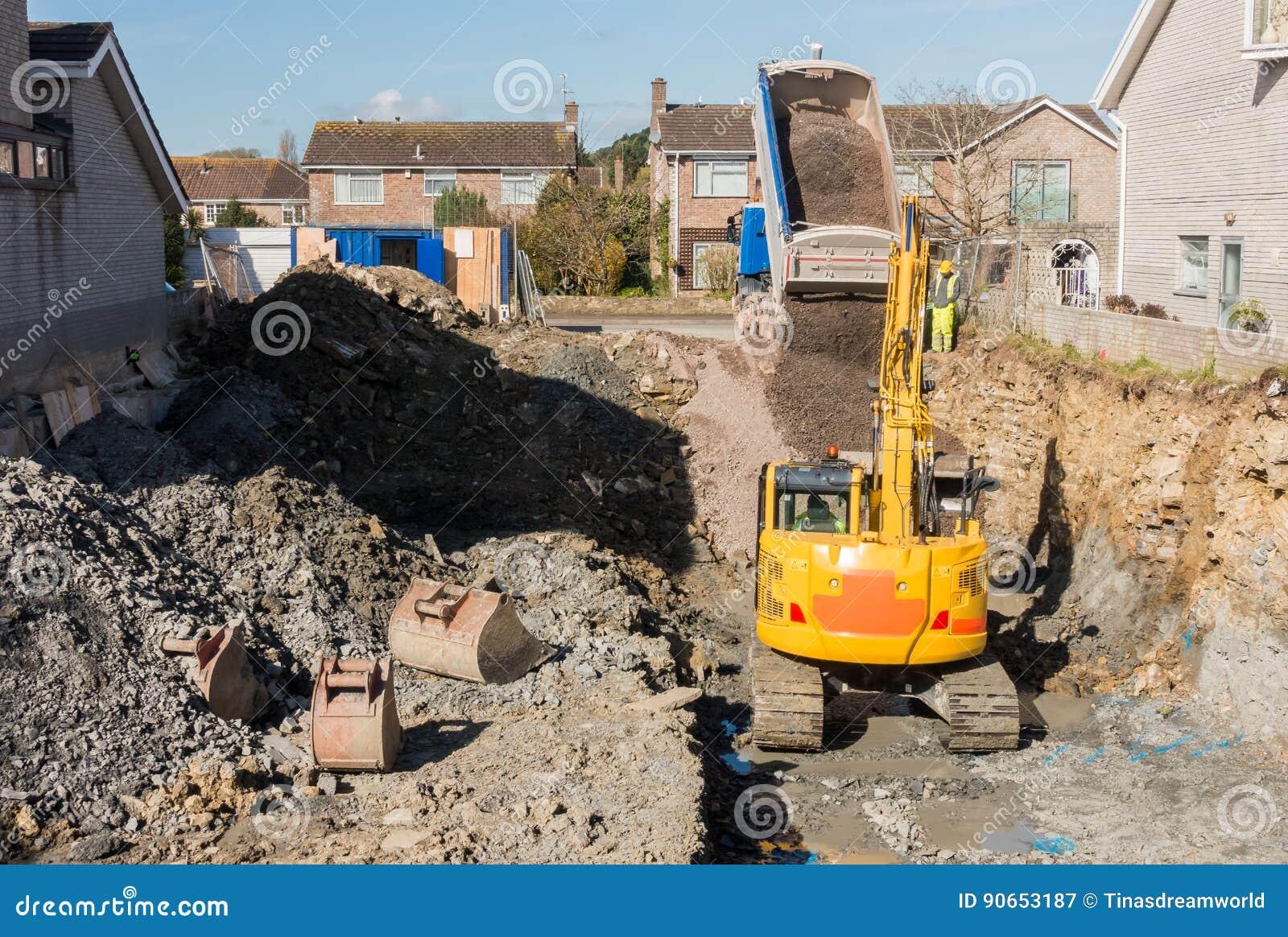 Graafwerktuig Digging terwijl de Kipwagenvrachtwagen leegmaakt