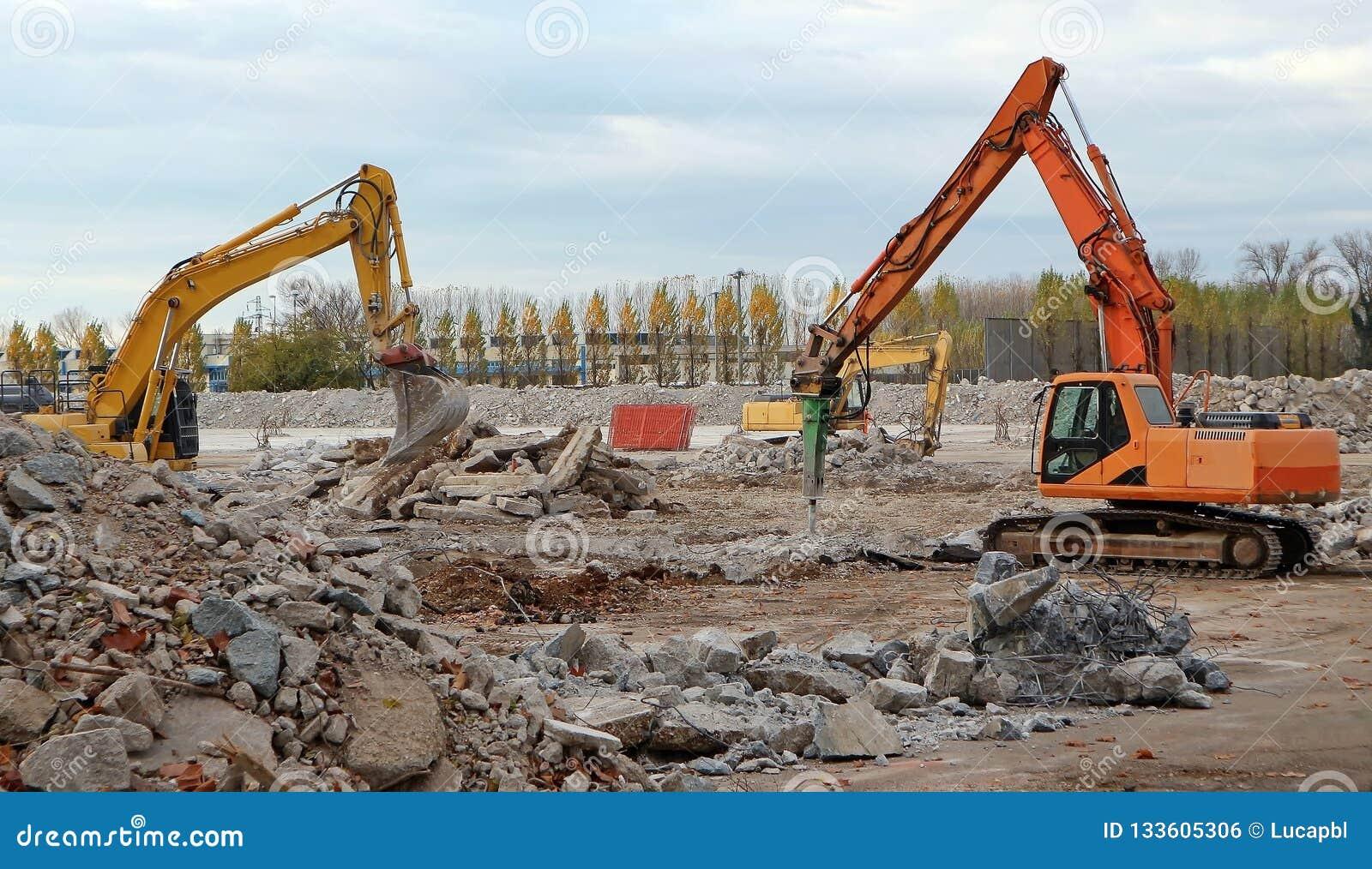 Graafwerktuigen die een grote oude industriezone voor een renovatie op een toekomstig commercieel gebied ontmantelen