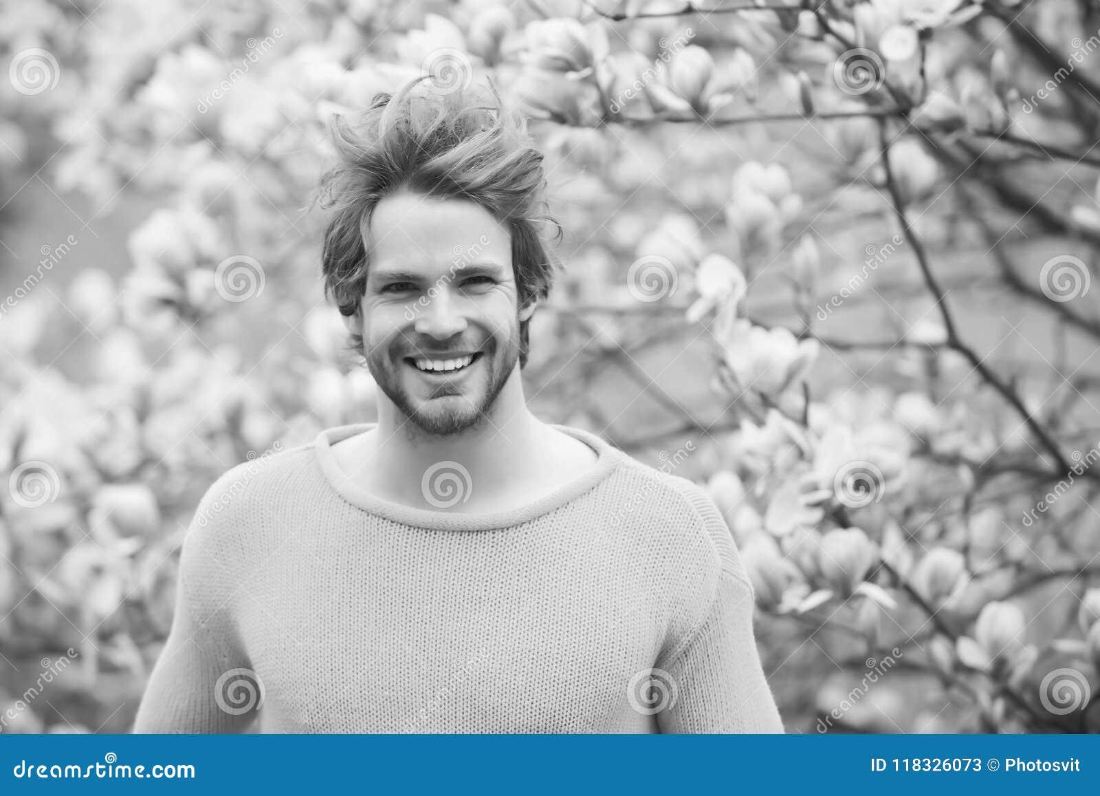 Grabb med skägget som ler i gul tröja på blom- bakgrund