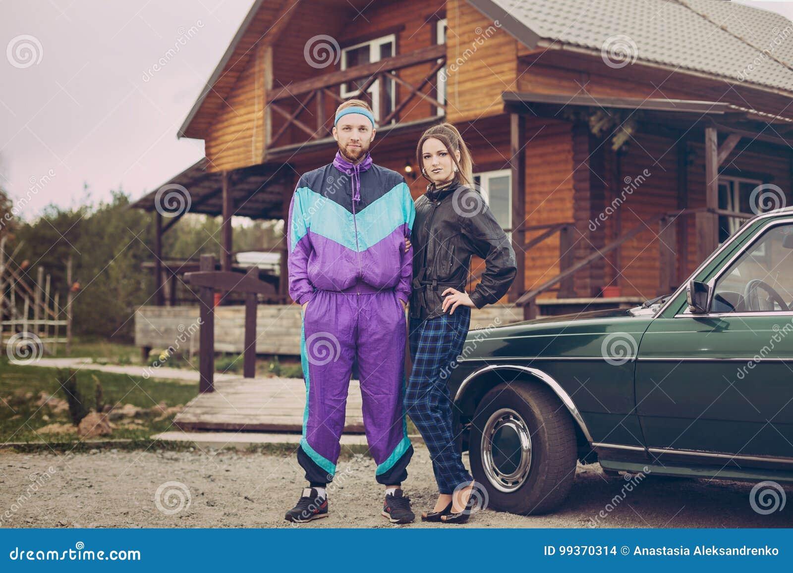 Grabb och flicka i kläder av ninetiesna, bredvid den gamla bilen
