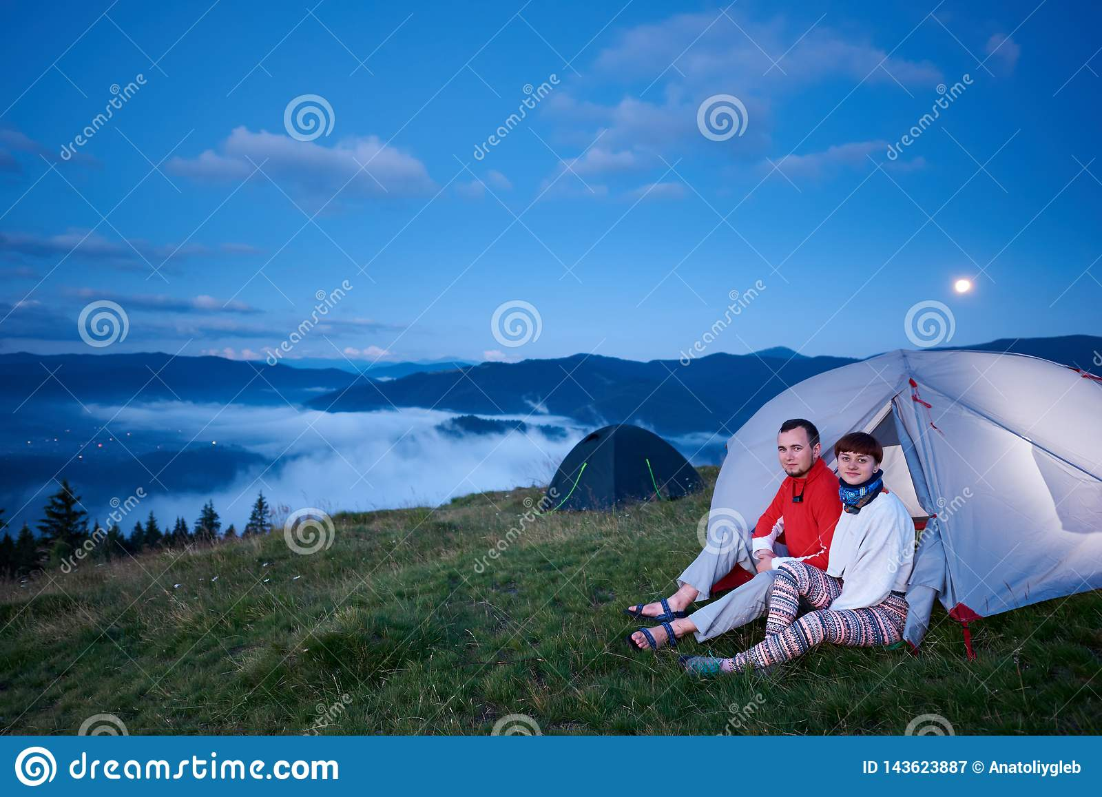 Grabb och flicka som sitter i tält på gryning med sikt av det härliga landskapet
