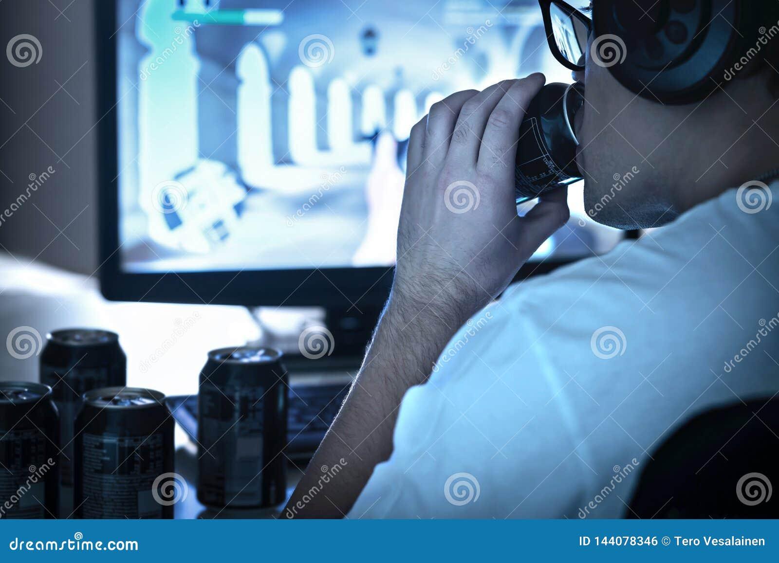 Grabb som dricker sodavatten och spelar videospelet eller som håller ögonen på den online-levande strömmen För mycket energidrink