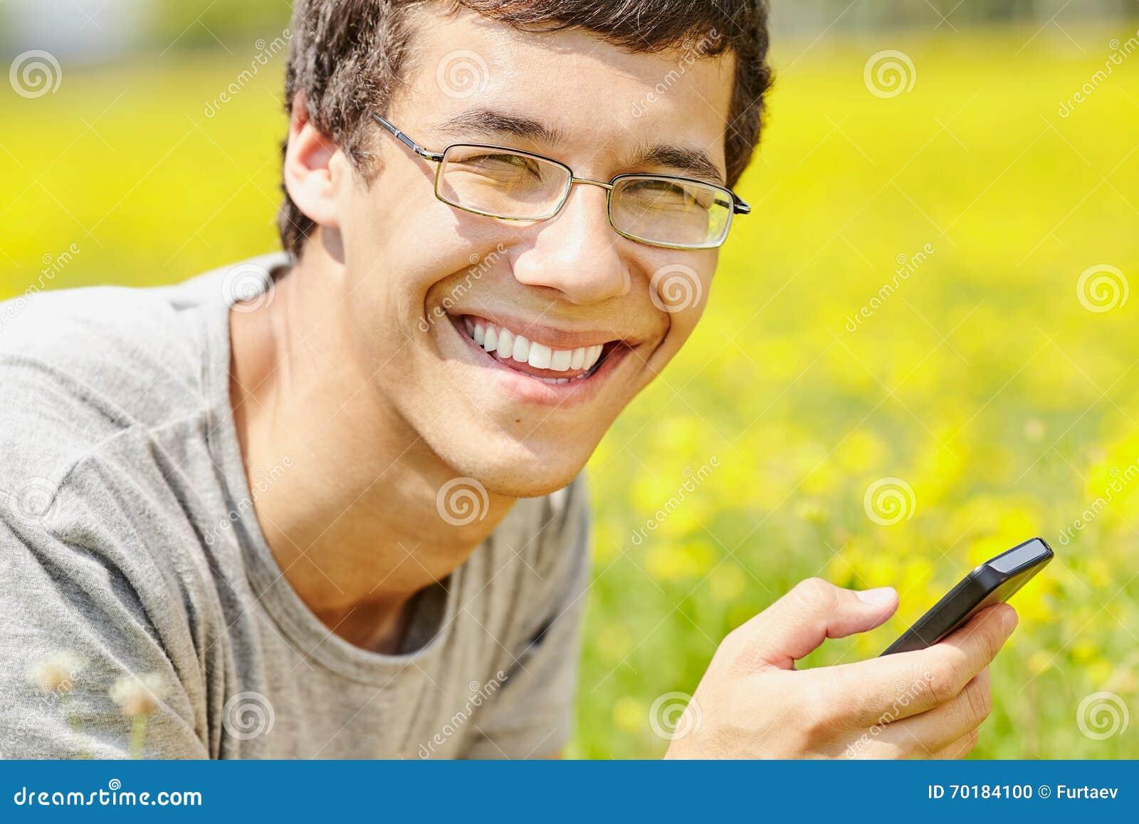 Grabb som smsar på mobiltelefonen
