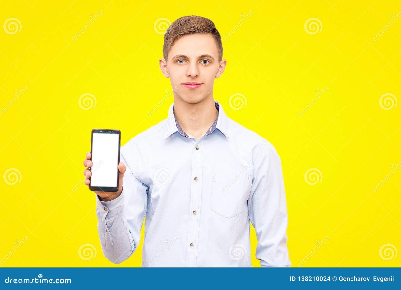 Grabben i den blåa skjortan annonserar telefonen som isoleras på en gul bakgrund