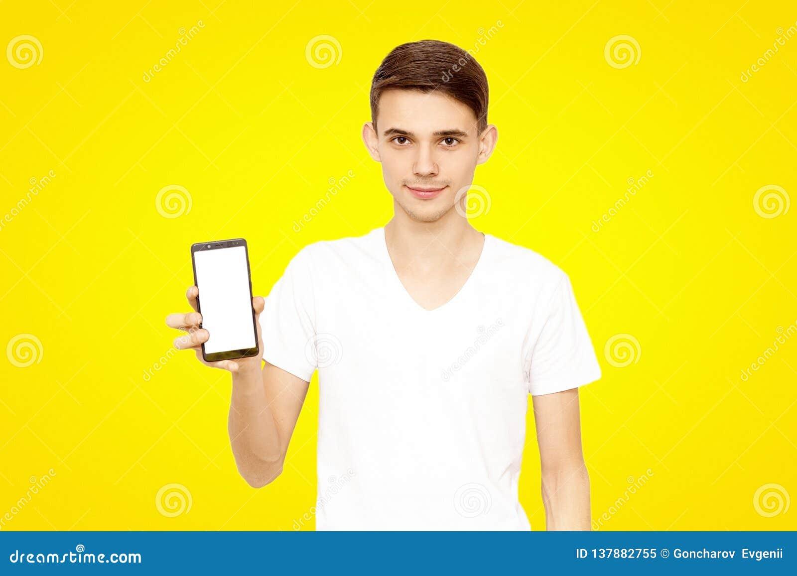 Grabben i den vita T-tröja annonserar telefonen, på en gul bakgrund